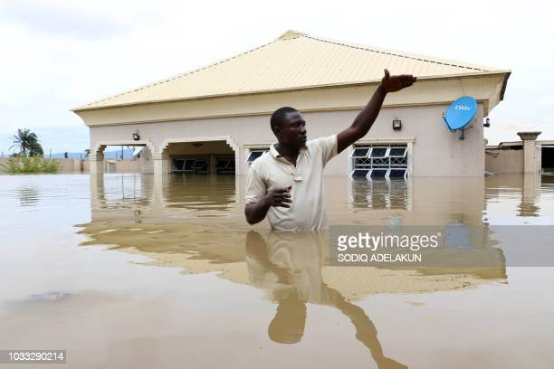 TOPSHOT A man gestures next to his flooded house following heavy rain near the Nigerian town of Lokoja in Kogi State on September 14 2018