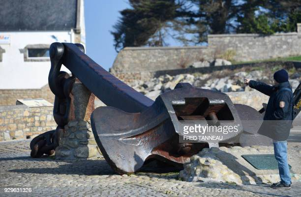 A man gestures next to the ancient anchor of the Amoco Cadiz February 22 2018 in Portsall western France On March 16 1978 the Liberian oil tanker...