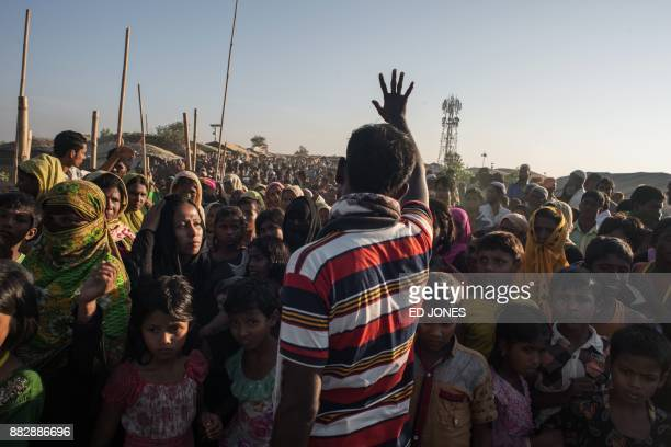 Man gestures telling Rohingya migrants queuing to recieve aid that the delivery has been cancelled, at the Kutupalong refugee camp at Cox's Bazar on...