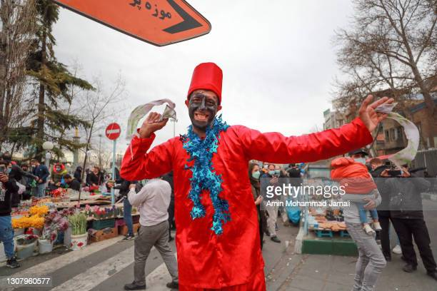 Man gestures to the camera as Iranian people get ready for Persian New Year on March 19, 2021 in Tehran, Iran. Nowruz is calculated according to a...