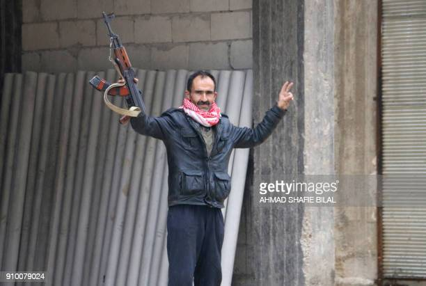 A man gestures while holding his rifle in the Syrian Kurdish town of Jandairis in the northern Afrin district on January 24 2018 Turkish forces and...