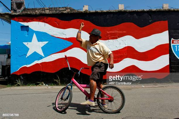 A man gestures while riding his bike in front of a mural with the Puerto Rican flag painted in the aftermath of Hurricane Maria in Loiza Puerto Rico...
