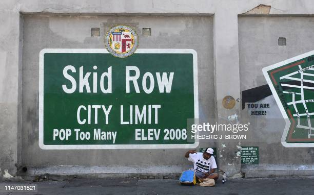 TOPSHOT A man gestures while seated beside a Skid Row painting on a sidewalk in downtown Los Angeles on May 30 2019 The city of Los Angeles on May 29...