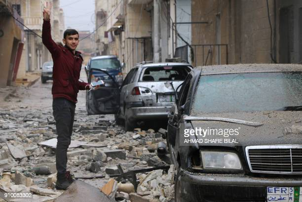 TOPSHOT A man gestures while standing amidst debris in the Syrian Kurdish town of Jandairis in the northern Afrin district on January 24 2018 Turkish...