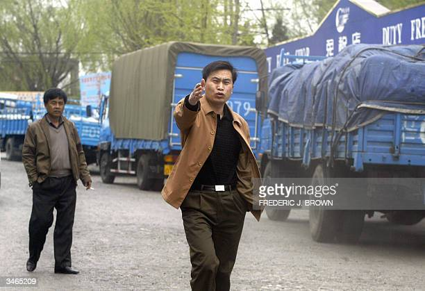 Man gestures while walking past a convoy of trucks loaded with supplies passing the Dandong border checkpoint bound for North Korea, 25 April 2004,...