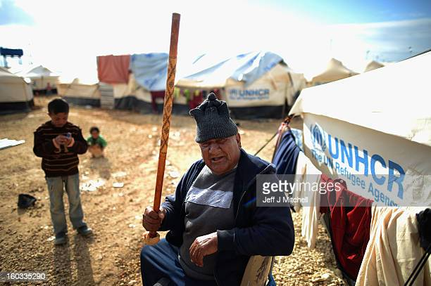 A man gestures with his stick as Syrian refugees go about their daily business in the Za'atari refugee camp on January 29 2013 in Mafraq Jordan...