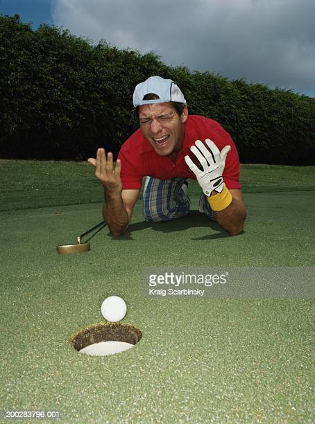 Man gesturing beside golf ball at edge of hole on putting green