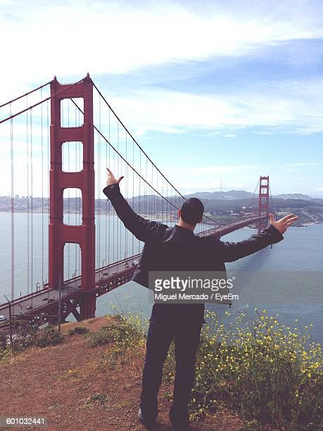 Man Gesturing In Front Of Golden Gate Bridge Over River Against Sky