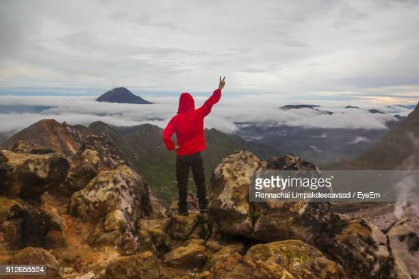 Man Gesturing Peace Sign While Standing On Rock Against Sky