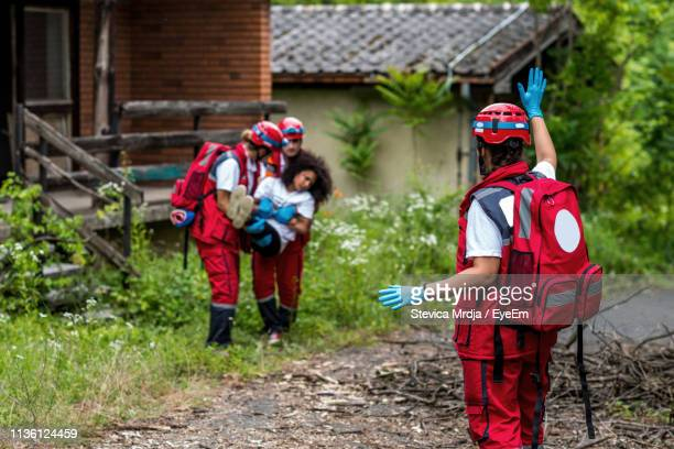 man gesturing towards rescue workers carrying injured woman during tornado - rescue worker stock pictures, royalty-free photos & images