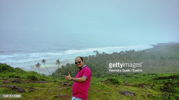 man gesturing while standing on mountain against sea during foggy weather - gode photos et images de collection