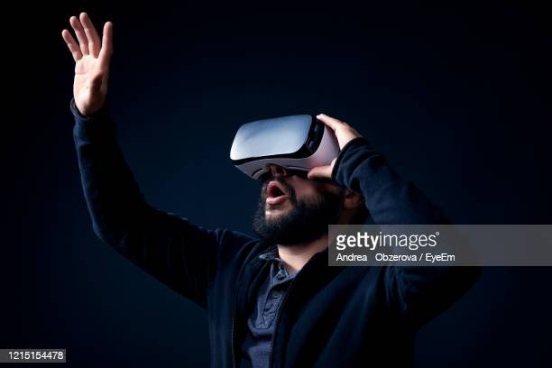 man gesturing while wearing very glasses against black background - one man only stock pictures, royalty-free photos & images