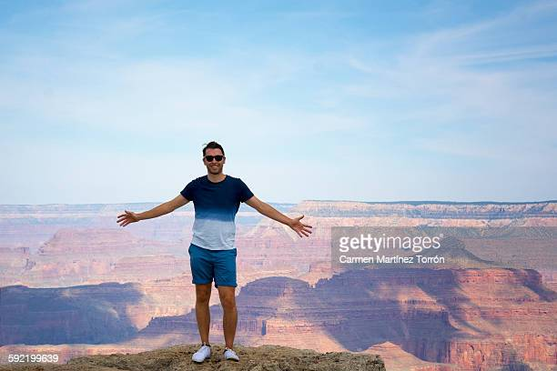 man gesturing with raised arms at grand canyon - carmen bella foto e immagini stock