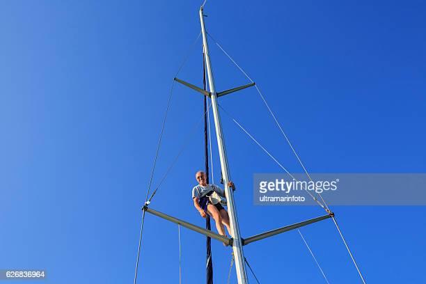 Mann Aufstehen auf der Mast und tun repairations