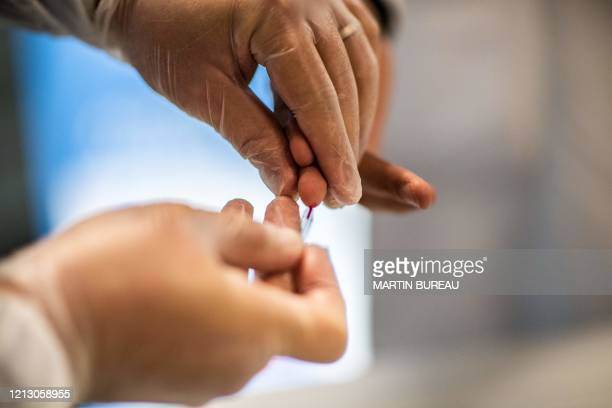 A man gets a blood sample with SARSCov2 blood test manufactured by the AAZ company in VilliersLeBel north of Paris on May 15 2020 five days after...