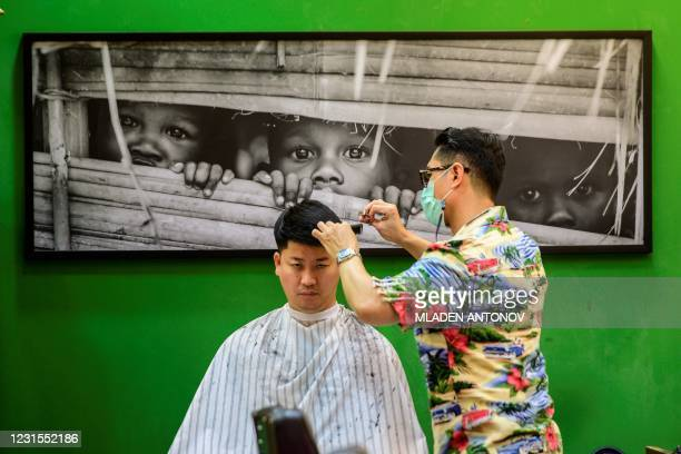Man gets a haircut in a barber shop in Bangkok on March 6, 2021.