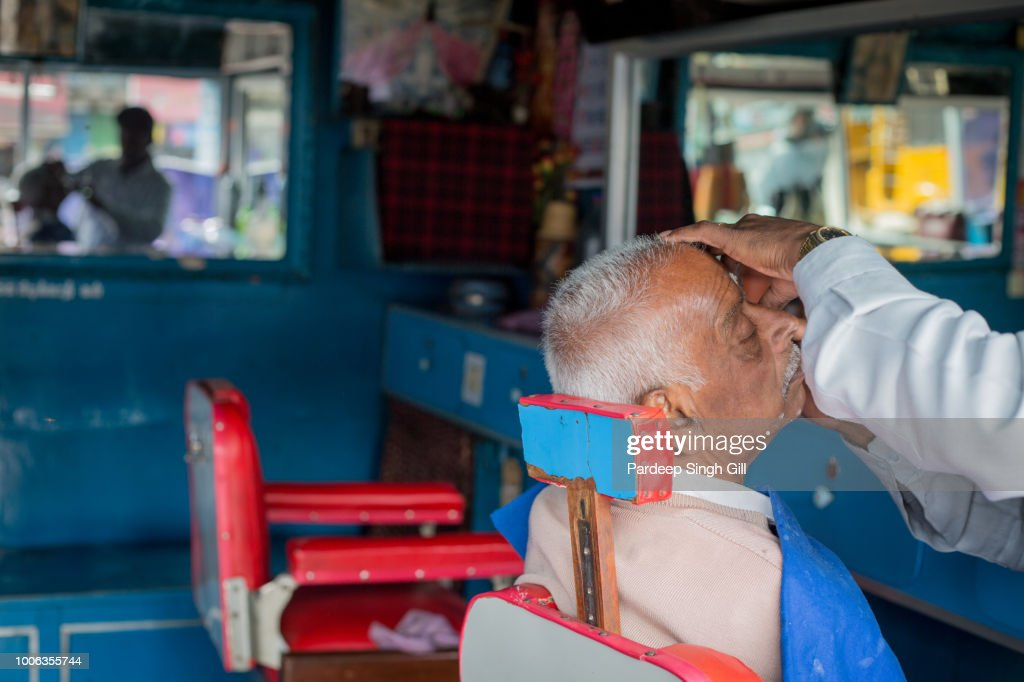 A Man Gets A Haircut In A Barber Shop In The Local Market Of Ooty