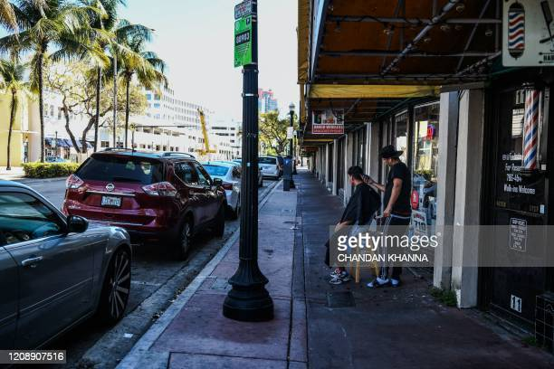 A man gets a haircut sitting outside of a barber shop on the pavement in South Beach Miami amid fears over the spread of the novel coronavirus on...