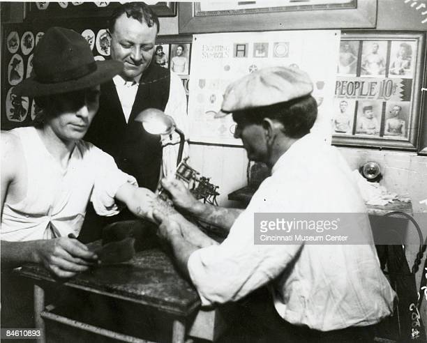 A man gets a tattoo upon his forearm in a parlor located on Vine Street below Canal Cincinnati Ohio 1919