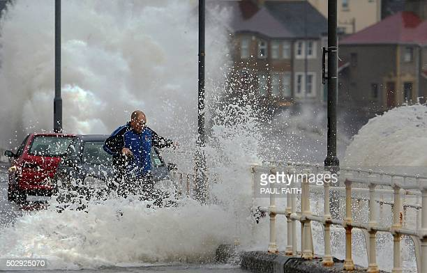 A man gets caught in spray as hide tide breaches the sea wall throwing up debris and flooding the main road in the coastal village of Carnlough in...