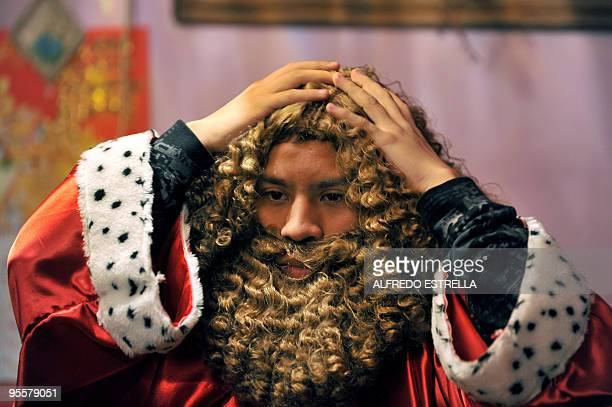 A man gets dressed as Melchior one of the Three Wise Men in Mexico City's Guerrero neighbourhood before a walk around the capital on January 3 2010...
