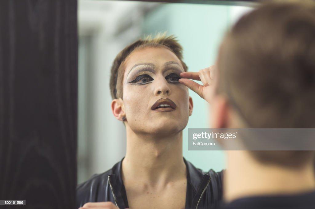 Man gets dressed in drag attire in bathroom : Stock Photo