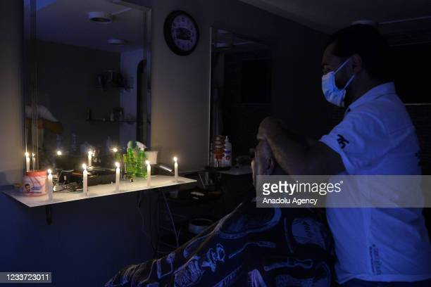 Man gets his hair cut in the dark during power cuts due to the fuel shortage and problems in the supply of fuel, which is traded in dollars, in...