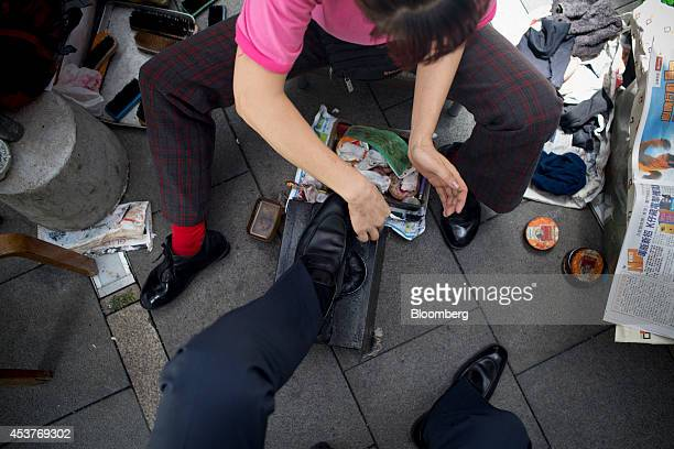 A man gets his shoes shined in the business district of Central in Hong Kong China on Monday Aug 18 2014 Slowing economic growth and rising...