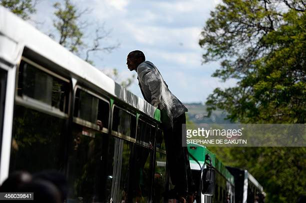 A man gets on the top of a packed bus after learning that we would not be able to board to pay his respect to South African former president Nelson...