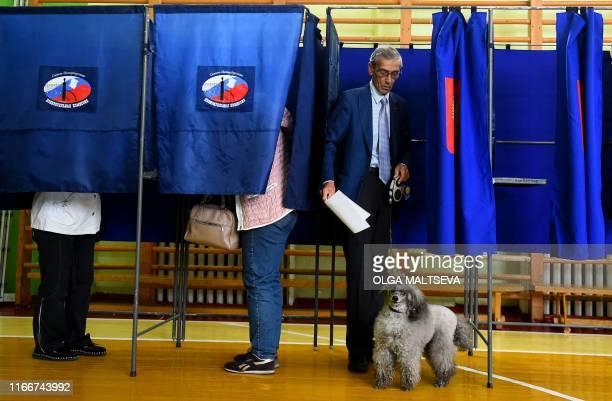 TOPSHOT A man gets out of a polling booth prior to casting his vote at a polling station during the governor's election in Saint Petersburg on...