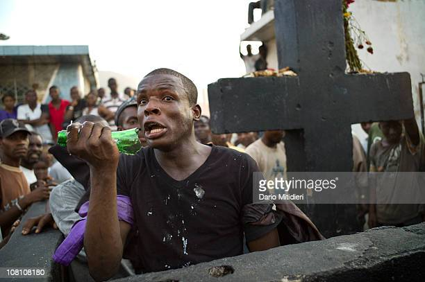 A man gets possesed by Gede next to a cross dedicated to Baron Samedi in the National Cemetery of PortauPrince Haiti on All Saints' Day Nov 1 where...