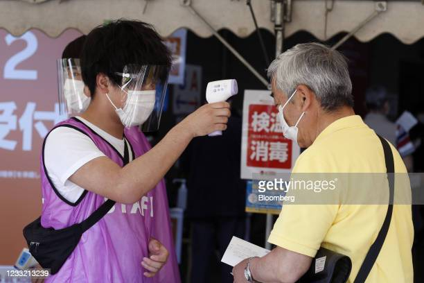Man gets temperature taken prior to receiving a dose of the Pfizer-BioNTech Covid-19 vaccine at an inoculation site at a mass inoculation site at...