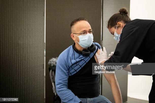 Man gets vaccinated inside the Paris Stade de France following its conversion into a Covid-19 vaccination centre on April 7, 2021 in Saint-Denis,...