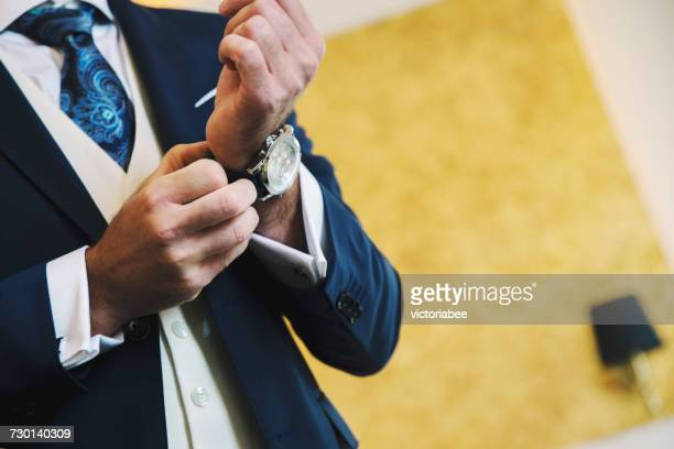 man getting dressed for his wedding - tijdmeter stockfoto's en -beelden
