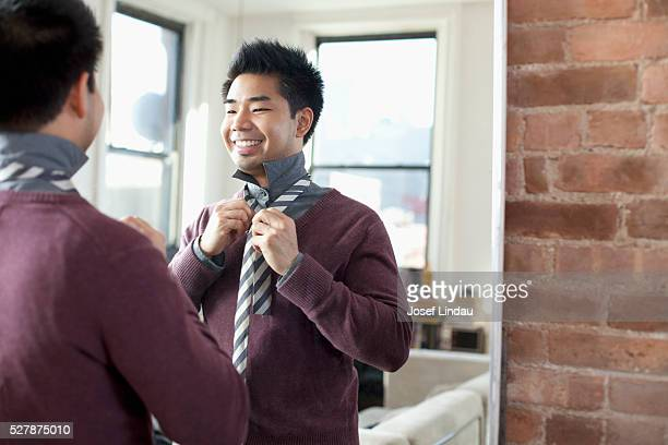 Man getting dressed in front of mirror