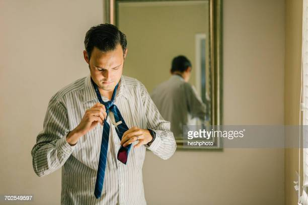 man getting dressed, putting on neck tie - heshphoto imagens e fotografias de stock