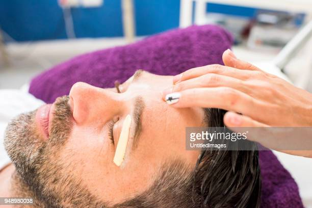 man getting eyebrows waxed - wax stock pictures, royalty-free photos & images