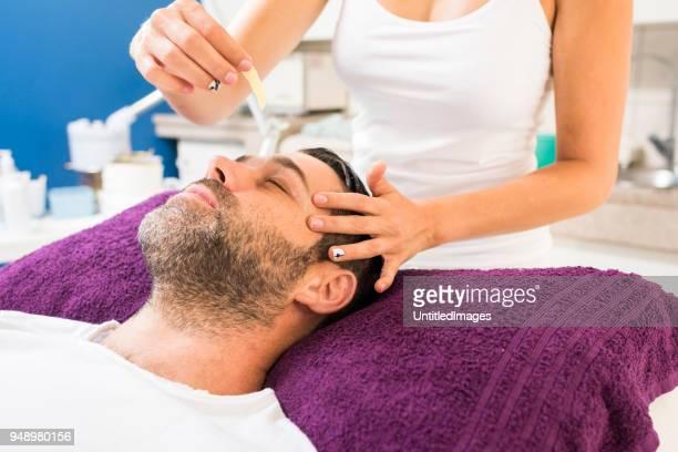 Man getting eyebrows waxed