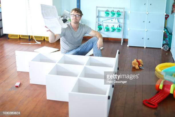a man getting frustrated with the instruction manual. - furniture stock pictures, royalty-free photos & images