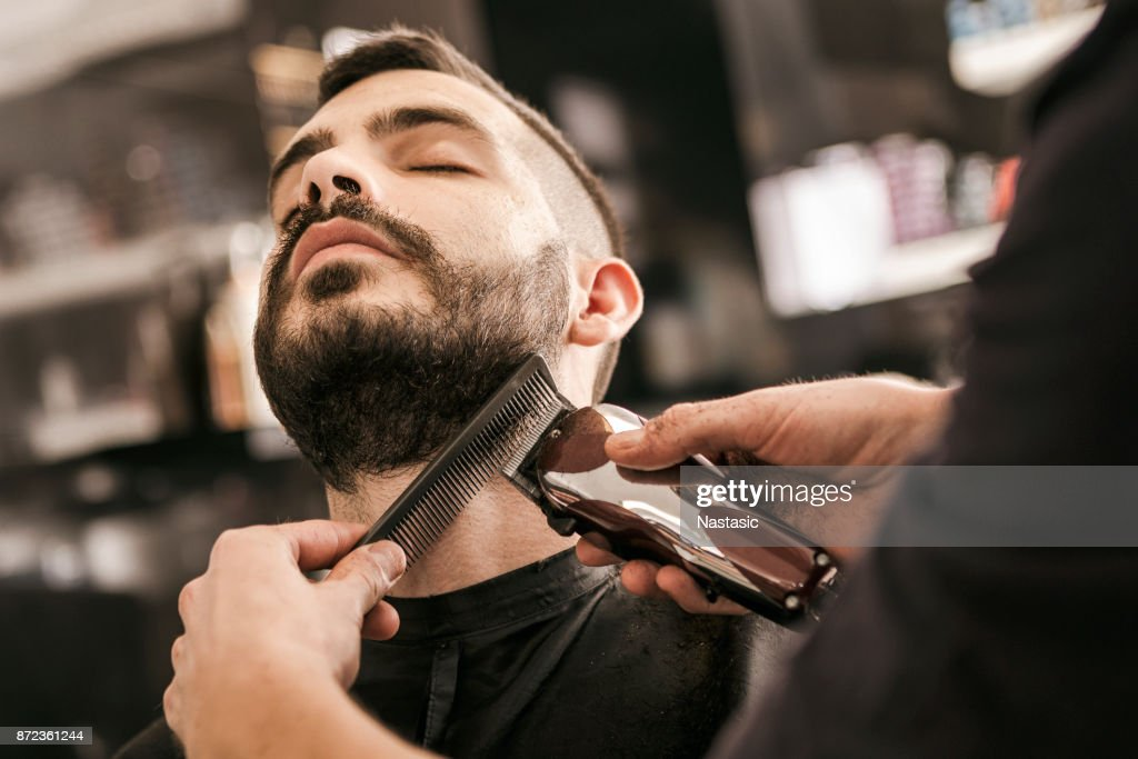 Hombre de recibir su barba cortan con máquina de afeitar eléctrica : Foto de stock