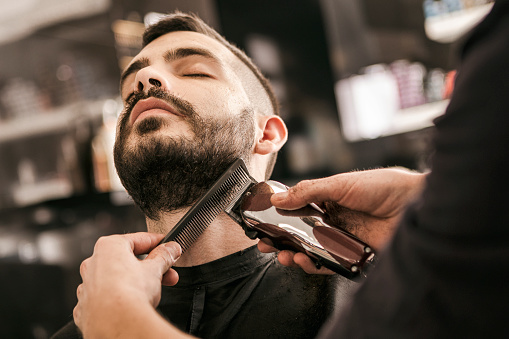 Man getting his beard trimmed with electric razor 872361244