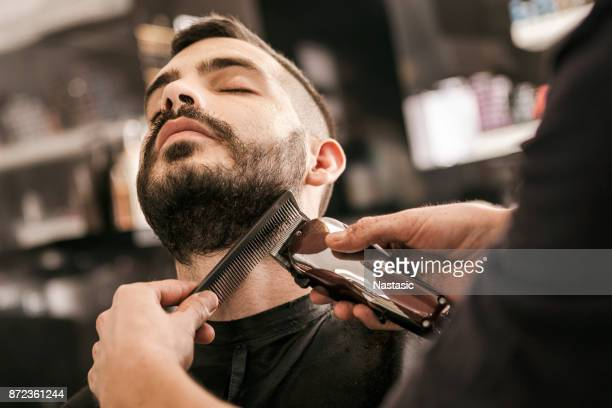man getting his beard trimmed with electric razor - barba peluria del viso foto e immagini stock