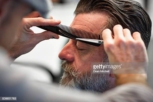 Man getting his eyebrows trimmed at barber shop