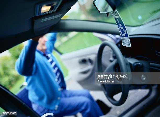 man getting into car - disabled sign stock photos and pictures