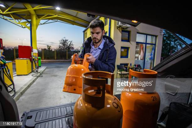 man getting out of car used gas butane cylinder containers - cylinder stock pictures, royalty-free photos & images