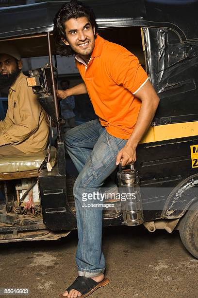 Man getting out of taxi, India