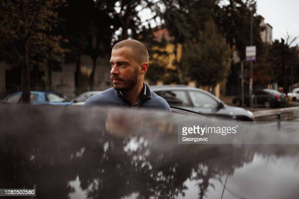 a man getting out of the car - leaving stock pictures, royalty-free photos & images
