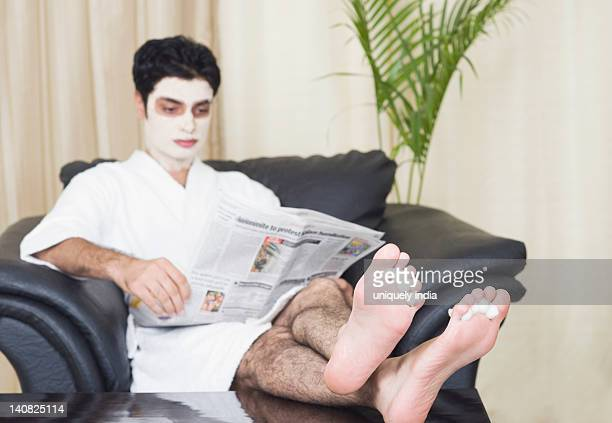 man getting pedicure while reading a newspaper - beautiful male feet stock photos and pictures
