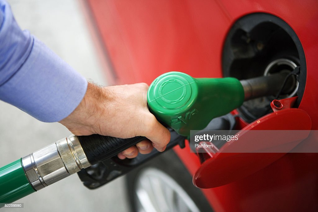 A man getting petrol into his red car Sweden. : Stock Photo