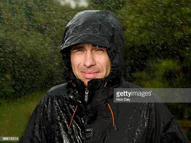 a man getting soaked in the rain - raincoat stock pictures, royalty-free photos & images